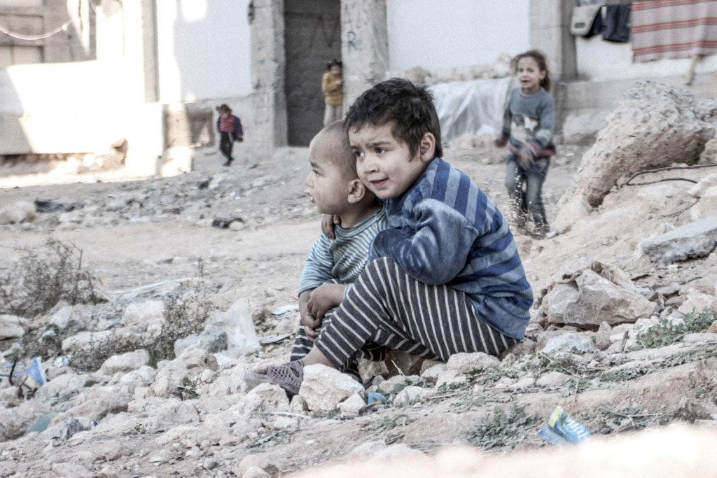 En Aleppo, Siria, Esraa de 4 años y su hermano Waleed de tres, se sientan en el suelo cerca de un refugio para los desplazados internos. Foto: UNICEF/ONU013175/Al-Issa