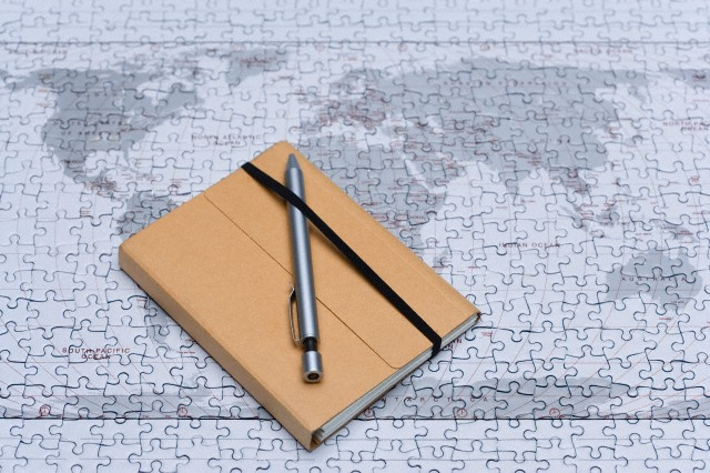 Diary with pen on jigsaw puzzle --- Image by © Sung-Il Kim/Corbis
